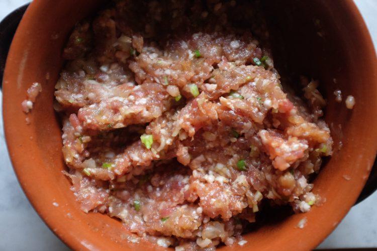 Metti tutti gli ingredienti asciutti (maiale, gamberi, zenzero, cipollotti, pepe del Sichuan, cinque spezie e sale fine), la salsa di soia, e la salsa di ostriche in una ciotola. E mescola.