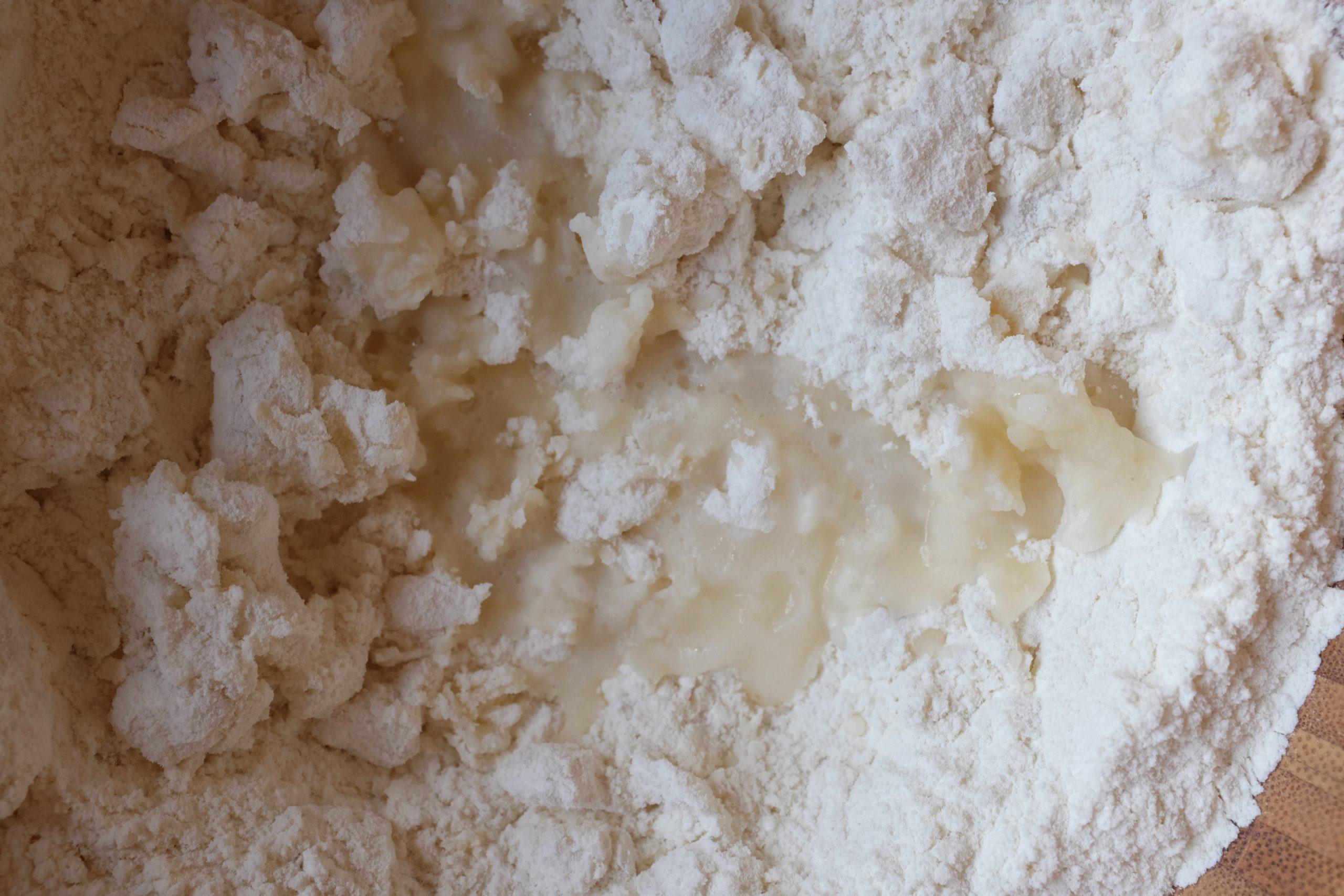 Aggiungi acqua bollente lentamente mentre mescoli per amalgamare. La farina così cotta ha una sembianza semi trasparente.