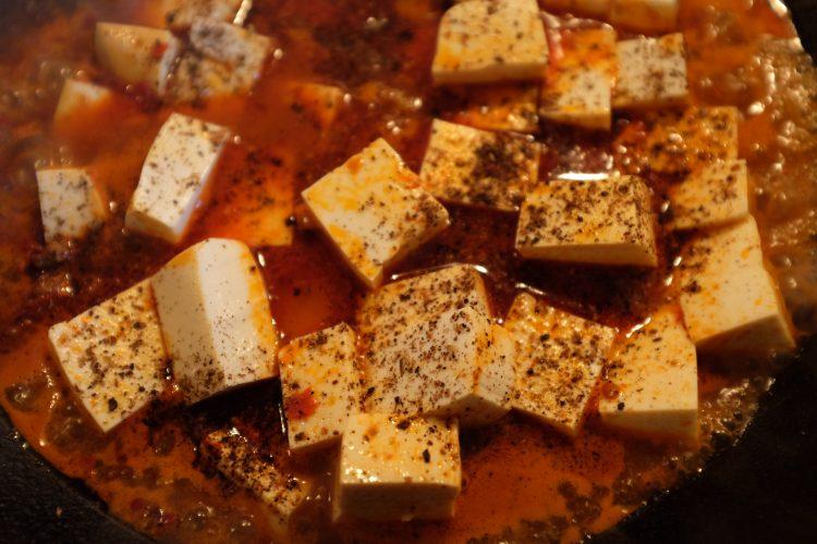 Spruzzaci sopra il pepe di Sichuan. Copri e continua a cuocere a fuoco lento per 10 minuti.