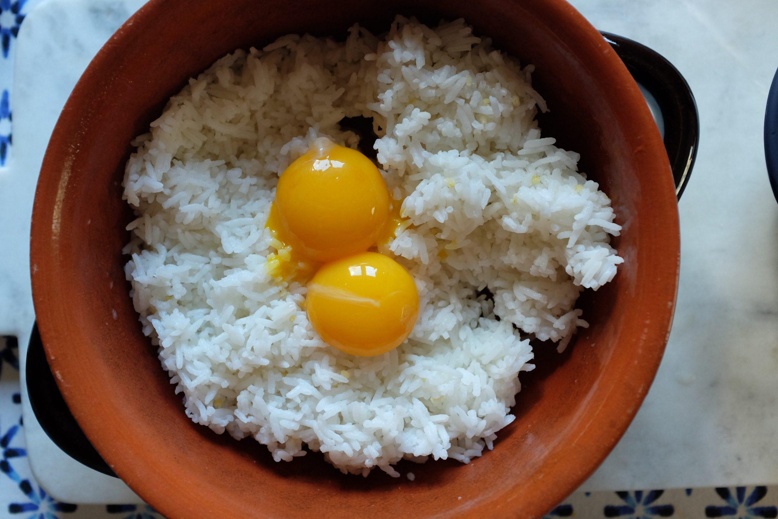 Metti il riso cotto il giorno prima in una ciotola. Spacca due uova e separa il tuorlo dall'albume. Gira il tuorlo nel riso uniformemente.