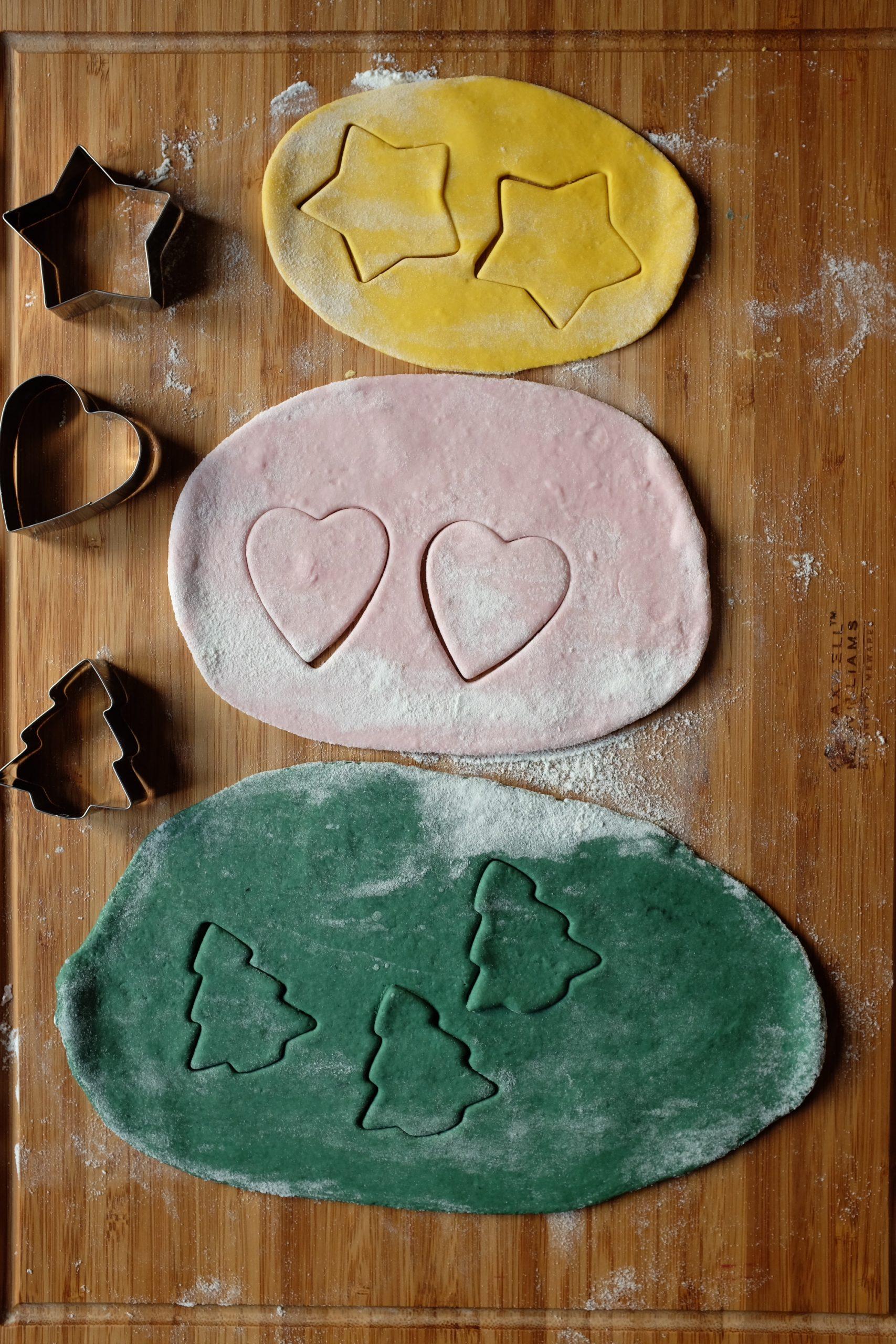 Stendi gli impasto in eccesso su una spianatoia appena infarinata utilizzando un mattarello. Taglia la pasta utilizzando le formine per biscotti di Natale della forma desiderata.