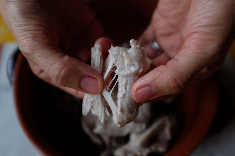Spengi il fuoco ed attendi che la temperatura dell'acqua scenda. Prendi il pollo, separa la carne dalle ossa.