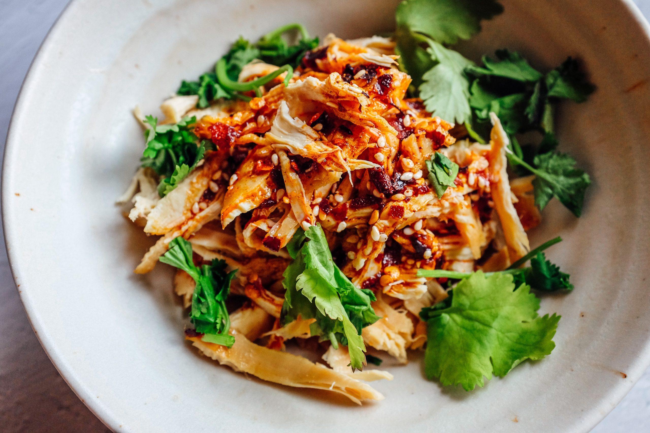 Condisce il pollo con 3 - 4 cucchiai d'olio piccante al peperoncino. Guarnisce con il coriandolo.