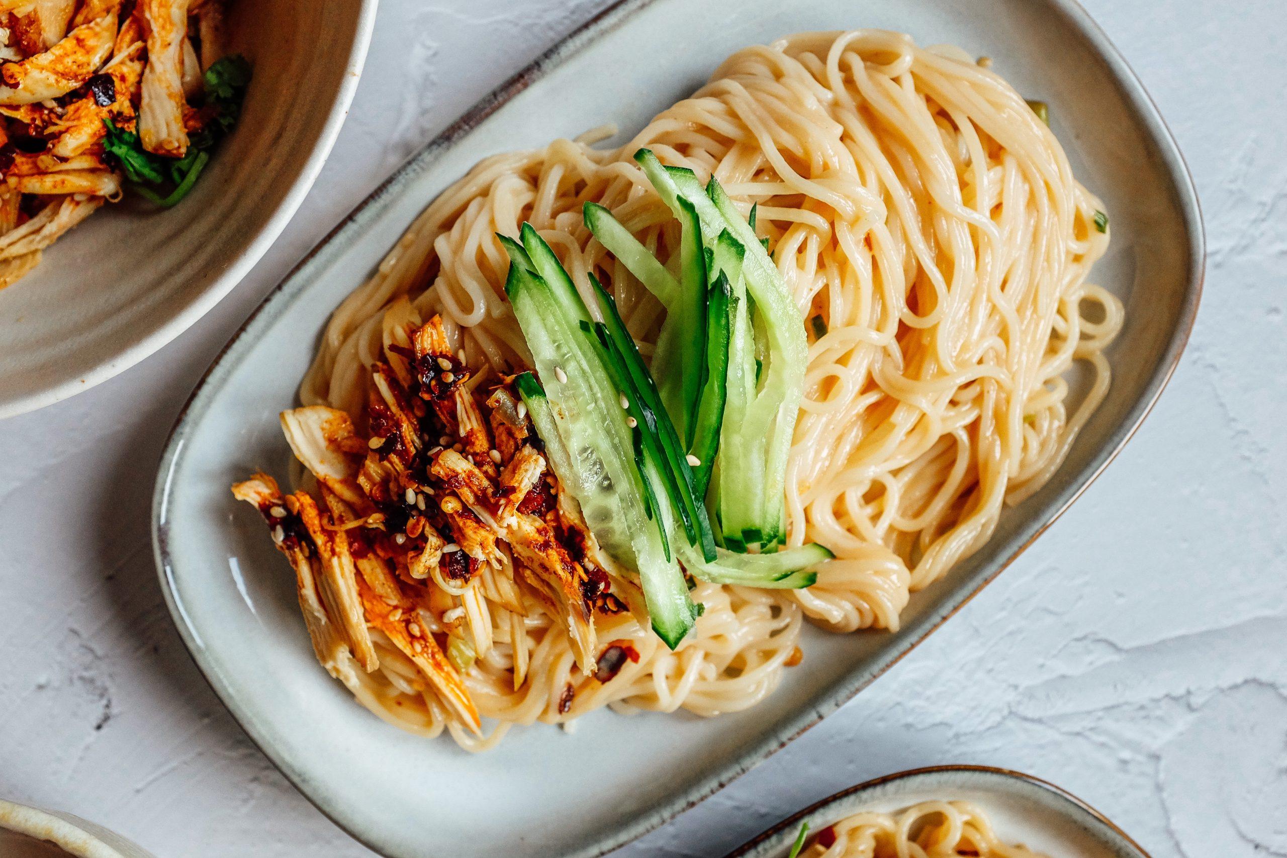 Scola i noodles e mettili in una ciotola. Aggiungi le sale, il cetriolo e il pollo piccante in base alle tue preferenze.