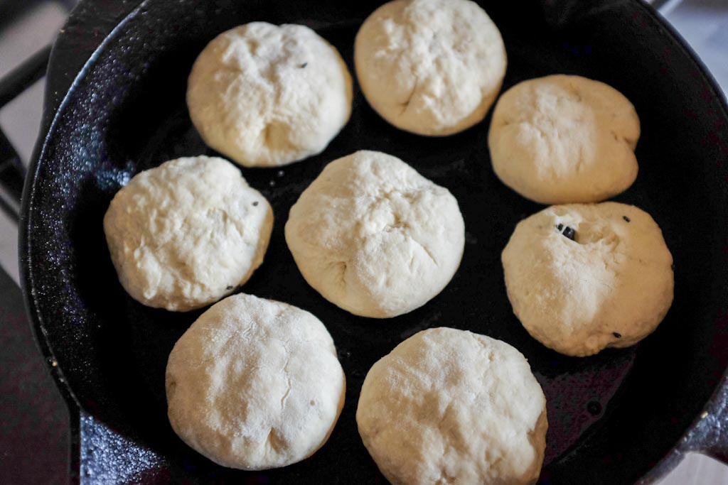 Metti le pizzette nella padella e friggi per 5 minuti a fuoco medio fino a che la base non sia dorata.