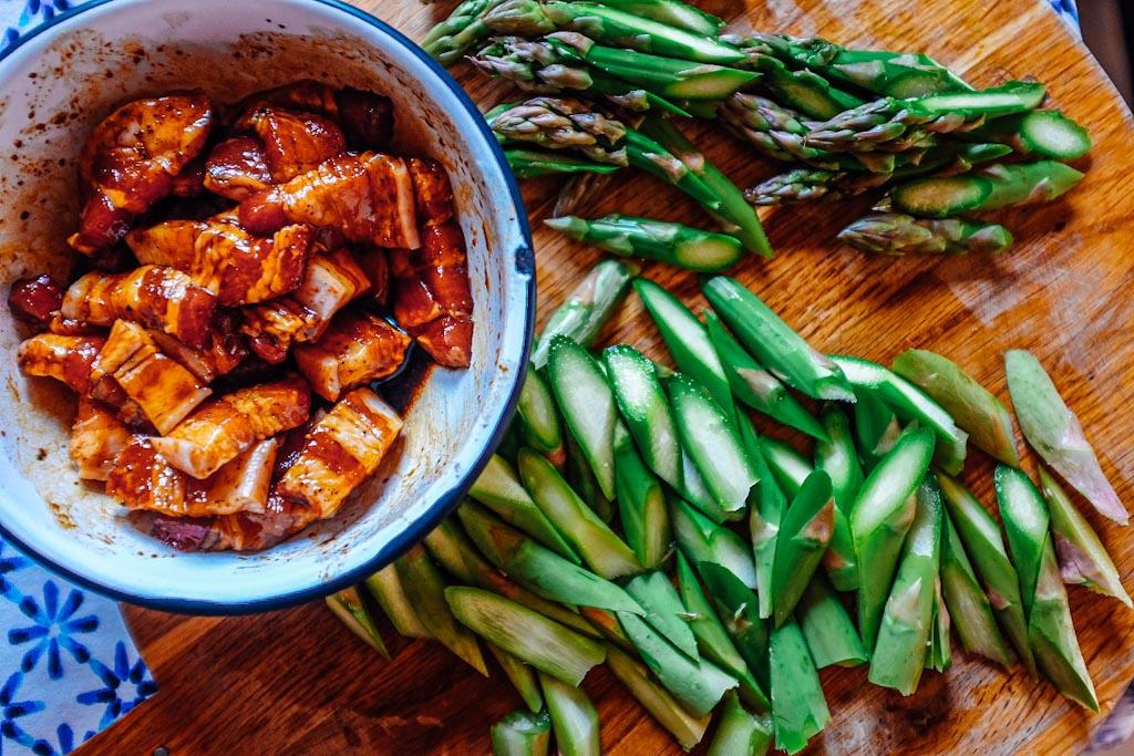 taglia la pancetta a fettine e falla marinare. Taglia gli asparagi
