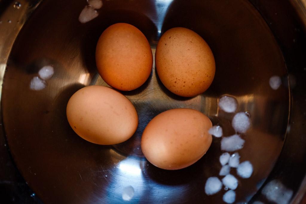 (dopo 5 minuti) Estrai le uova e mettile subito in un bagno di ghiaccio. Lasciale raffreddare completamente.