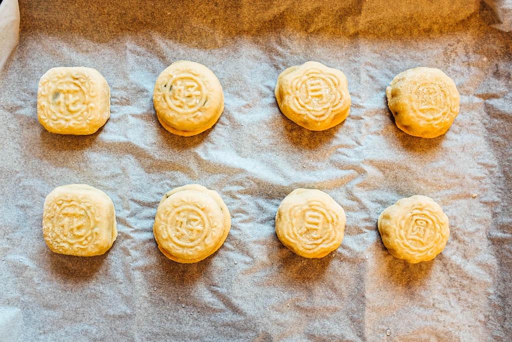 Riscalda il forno a 180°C. Spruzza un po' d'acqua sul mooncake. Cuoci i mooncake per 5 minuti.